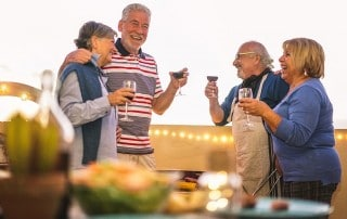 A group of elderly friends laughing while enjoying each others company while dining outside. While it's still important to have a active lifestyle as a senior, may have issues with bone resorption, especially with as a denture wearer.