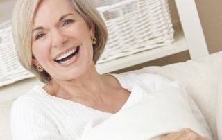 Older woman smiling while sitting on a couch and holding a pillow