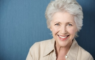 older woman with short hair smiling in front of plain background
