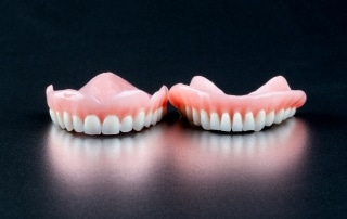 Top and bottom set of dentures laying next to each other on a table