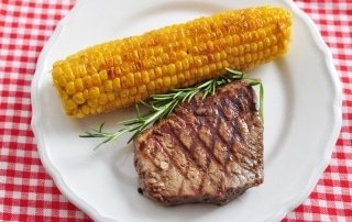 Corn on the cob and steak on a plate