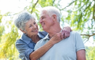Older couple smiling, with woman hugging man around the shoulders