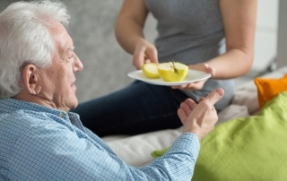 A woman handing an older man a plate with an apple cut in half