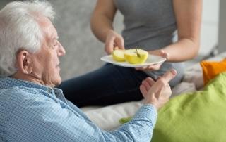 A woman handing an older man a plate with an apple cut in half