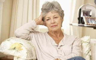 Older woman sitting in a chair with her head leaning on her hand, looking sadly down