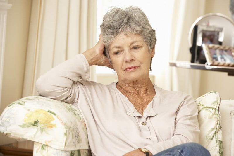 senior woman sitting on her couch, concerned