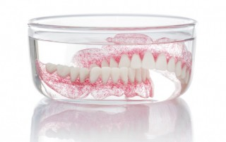 Dentures sitting in glass bowl to be clean