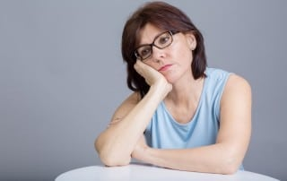 Sad woman sitting with head on hand because her dentures irritate her tongue