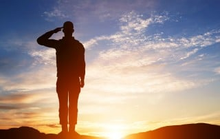 Man saluting on a hill, with horizon behind him
