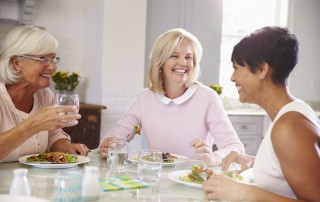 Three women sitting and laughing while having lunch
