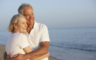 Older couple smiling and hugging on the beach