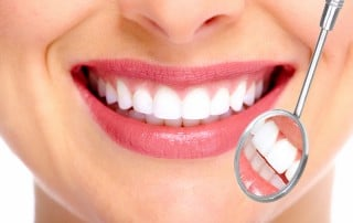 Close up of woman's smile next to dental mirror tool
