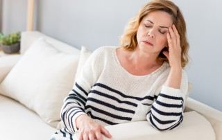 Woman sitting on couch with a headache, with eyes closed and hand on head