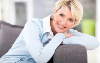 Woman sitting in a chair with her head rested on her arms, smiling