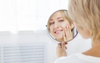 Girl smiling while touching her face and looking into a handheld mirror
