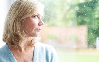 Older woman looking out rainy window