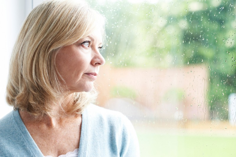 woman looking outside though a rainy window