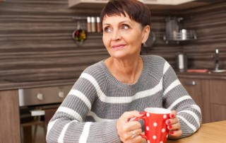 Older woman sitting at kitchen table with a cup