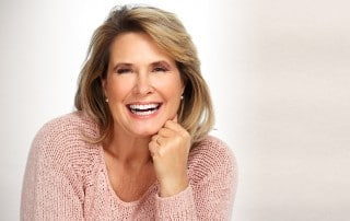 Beautiful smiling senior woman face over gray background.