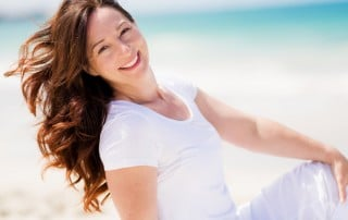 Woman with long hair sitting and smiling on the beach