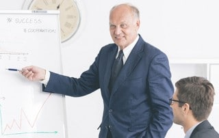 Man making a presentation close to the board with charts