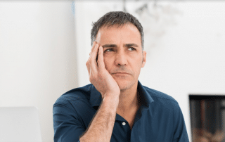 Man sitting with hand on his head and a sad face from ear pain
