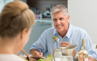 Man smiling while eating salad with his wife