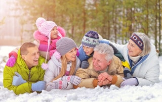 Grandparents with their children and grandchildren, laughing and smiling laying in the snow because FOY® Dentures have improved their quality of life