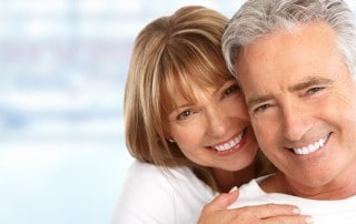 Older couple smiling because they have Dentures they Love