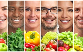 Beautiful people smiling behind fruits and vegetables that they can eat with FOY dentures