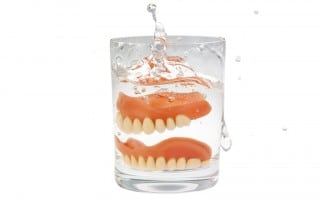 A cheap set of dentures being dropped in a glass of cleaner. Cheap Dentures can cause a number of problems.