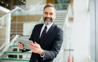Mature businessman with a salt & pepper beard smiling on a set of stairs. He's upgraded to a better denture!