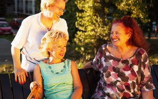 3 old friends laughing and joking on a bench in the warm sun. They are proud of their FOY® Dentures