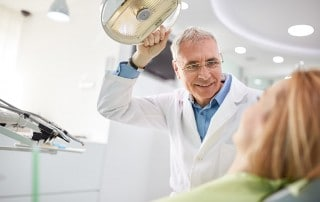 A Dentist adjusts his searchlight before beginning a denture reline procedure to help with a patients bite