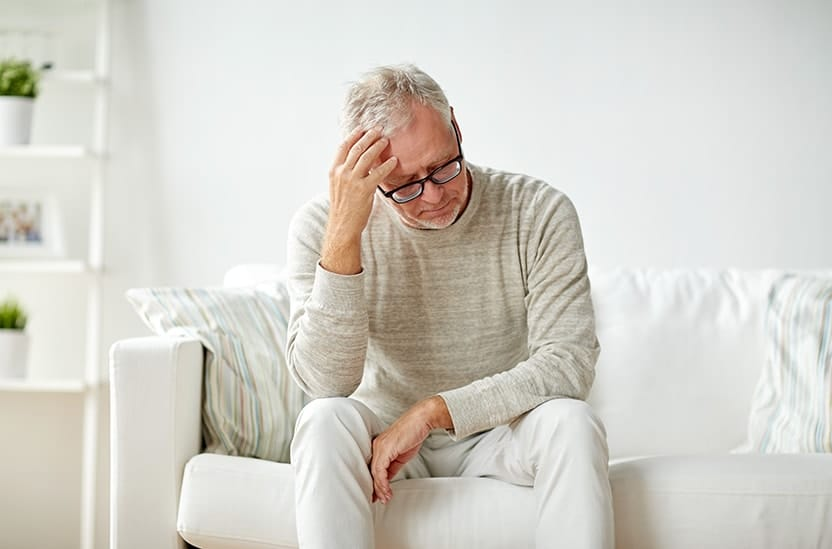 Older unhappy man resting his hand against his head staring down at the ground while sitting on a white couch. He's not happy with his implant dentures and now looking for the alternative of FOY ® Dentures