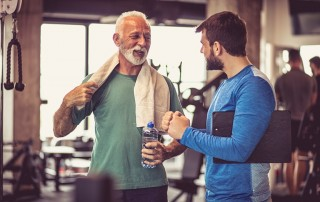 Active senior man finishing his workout at the gym while talking to a friend. With an active lifestyle, he doesn't want implants which is why dentures are his best option.