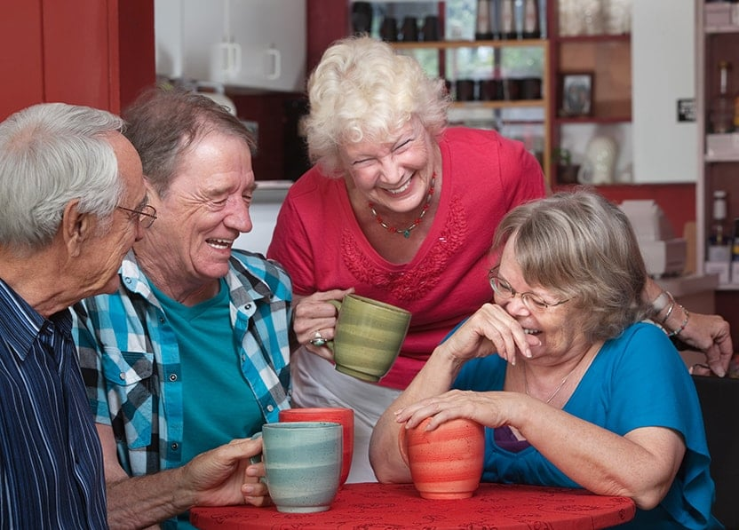 A group of old friends laughing and joking while having coffee together. They weren't looking for just any denture dentist near them, they were looking for a DFOY® dentist. Now they are smiling with confidence.