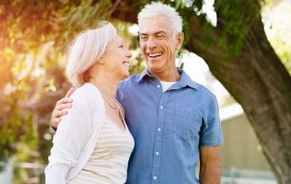 Senior couple in love, relaxing in park. The right kind of dentures can improve your love life
