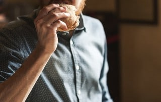 Man eating sandwich for lunch. If your dentures don't fit properly, they don't suction against your gums as well, and this can make them easier to dislodge making it hard to eat a Jersey Mike sub sandwich.