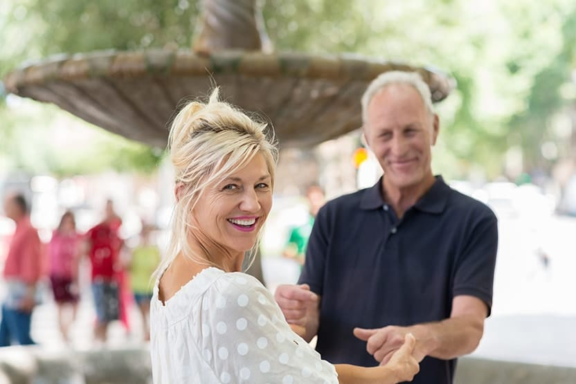 An older couple laughing and spending time with each other outside by a beautiful fountain. You wouldn't know by her smile but her Dentures Don't Have to Look Like Dentures Anymore!® and they don't have to feel Like Dentures Anymore, Either
