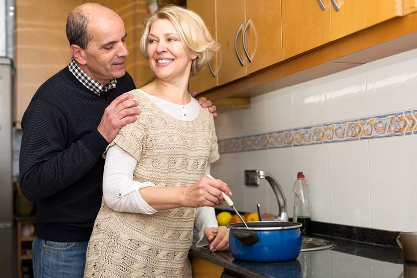 Retired couple talk in the kitchen while the wife makes soup for dinner. Not all dentures fit like FOY® so much that a man had emergency surgery after he swallowed his pair while eating soup.
