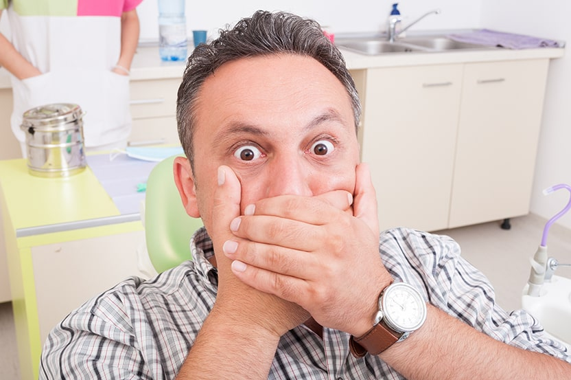 Man sitting at dental office being scared, ready for dentures. Don't be afraid of dentures with FOY® Dentures.