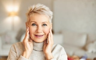 Mature blonde woman touches he plump cheeks in amazement