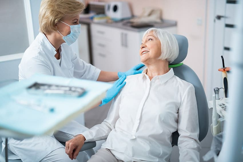 senior woman being friendly with her denture dentist during a visit