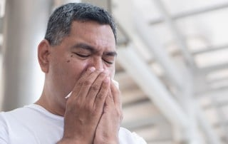 Man sneezing into his hand