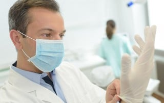 Dentist preparing for a patient by putting gloves on