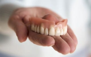 an upper denture resting on a hand