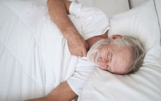 man sleeping on his back with a sore throat