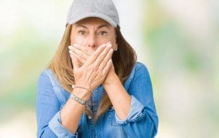 mature woman in baseball hat covering her mouth