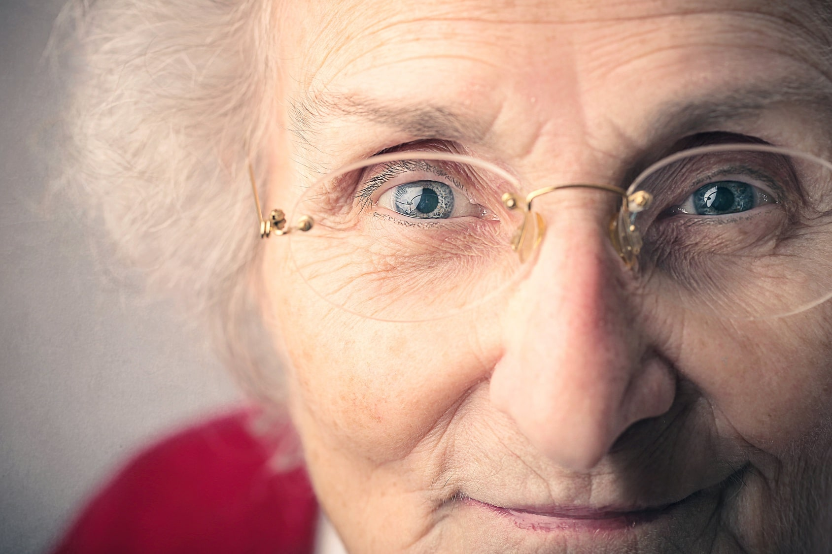 Close up of the face of an older woman with glasses